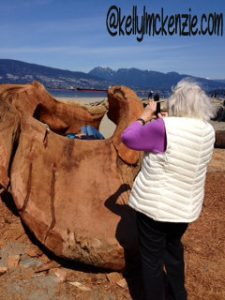 Mom taking photos of carved logs at Spanish Banks http://kellylmckenzie.com/the-importance-of-a-curious-mind/